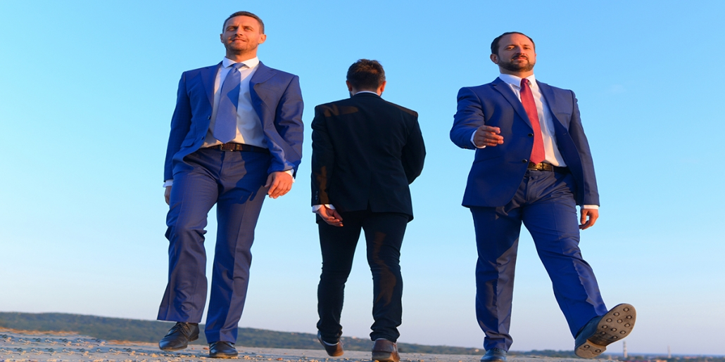 Three men dressed in suits walking accross open ground. Two facing front and one facing back.