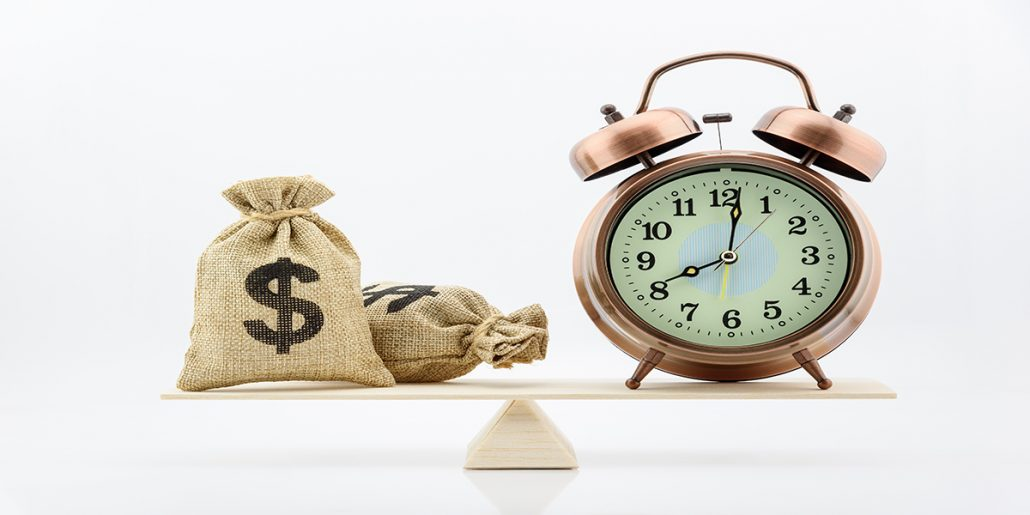 Two burlap bags with dollar signs on a balancing apparatus with an alarm clock on one end.